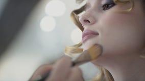 Close-up van vrouw die haar en samenstelling op haar gezicht met borstel leggen stock footage