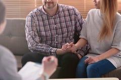 Close-up van vrouw en man holdingshanden op een laag tijdens een psyc stock afbeelding