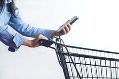 Close-up van vrouw met boodschappenwagentje en het winkelen lijst in smartph Stock Afbeelding