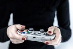 Close-up van vrouw met rood nagellak die een gokkencontrolemechanisme met Super Nintendo retro ontwerp het spelen videospelletjes royalty-vrije stock foto