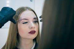 Close-up van vrouwelijk gezicht tijdens de procedure van de wenkbrauwcorrectie Royalty-vrije Stock Foto