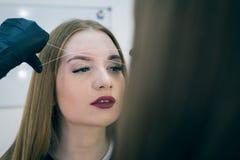 Close-up van vrouwelijk gezicht tijdens de procedure van de wenkbrauwcorrectie Royalty-vrije Stock Afbeeldingen
