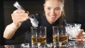 Close-up van vrouwelijke barman wordt geschoten die ijs zetten in alcoholische drank in langzame motie die de cocktails met geest stock footage