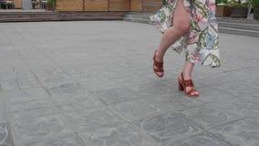 Close-up van vrouwelijke benen die in de ontwikkelende kleding lopen stock footage
