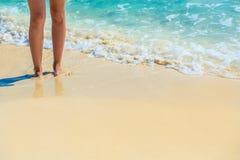 Close-up van vrouwelijke benen op tropisch strand De benen van vrouwen op sa Stock Afbeeldingen