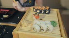 Close-up van vrouwelijke hand die eetstokjes gebruiken die ingelegde gember eten stock video