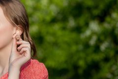 Close-up van Vrouwelijke Handen die Gehoorapparaat in Oor zetten Moderne digitaal in het oorgehoorapparaat voor doofheid en hard  stock afbeelding