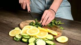 Close-up van vrouwelijke handen die muntbladeren op een scherpe raad naast gesneden komkommers en citroenen snijden Gezond en Gez stock videobeelden
