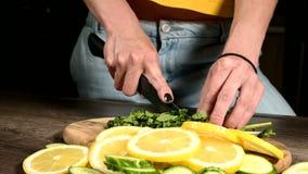 Close-up van vrouwelijke handen die muntbladeren op een scherpe raad naast gesneden komkommers en citroenen snijden Gezond en Gez stock video