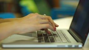 Close-up van vrouwelijke handen die tekstbericht op laptop typen binnen, jonge vrouwelijke studentenzitting op de bibliotheektred stock videobeelden