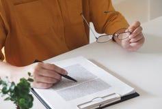 Close-up van vrouwelijke handen het schrijven van iets en het houden van glazen in haar bureau royalty-vrije stock foto