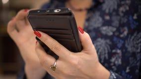 Close-up van vrouwelijke handen wordt geschoten die De vrouw met rode manicure schrijft berichten in smartphone De jonge vrouw ho stock videobeelden