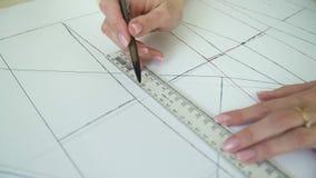 Close-up van vrouwelijke kleermakershanden die naaiend patroon trekken op papier stock video