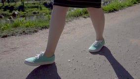 Close-up van vrouwen` s voeten in tennisschoenen Het meisje is op de asfaltweg langs de waterkant stock footage