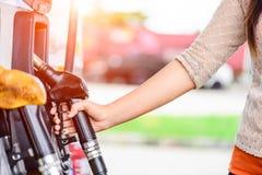 Close-up van vrouwenhand die een brandstofpomp houden bij een post royalty-vrije stock afbeeldingen