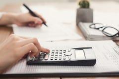 Close-up van vrouwenhand het tellen op calculator Royalty-vrije Stock Afbeeldingen