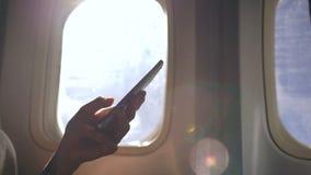 Close-up van vrouwenhanden die dichtbij vliegtuigvenster zitten die mobiele telefoon met behulp van tijdens vlucht stock footage