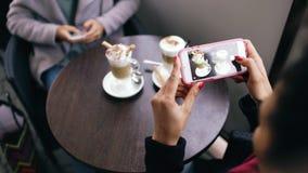 Close-up van vrouwenhanden die koffiekop fotograferen die smartphone gebruiken terwijl in openlucht het zitten in straatkoffie Royalty-vrije Stock Afbeeldingen