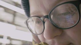 Close-up van vrouwenogen wordt geschoten in glazen die op het scherm dat van een werkende smartphone wijzen stock video