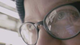 Close-up van vrouwenogen wordt geschoten in glazen die op het scherm dat van een werkende smartphone wijzen stock footage