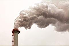 Close-up van vuile donkere rookwolken van een hoge industriële schoorsteen Royalty-vrije Stock Foto