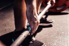 Close-up van weightlifter die handen slaan vóór barbelltraining bij de gymnastiek Stock Foto's
