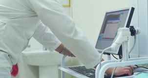 Close-up van werkende doktershanden met PC en apparaten De mannelijke arts werkt aan een PC in een laboratorium stock videobeelden