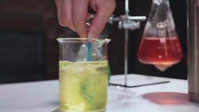 Close-up van wetenschapper die chemische oplossing voor experiment mengen bij laboratorium stock videobeelden
