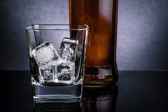 Close-up van whisky met ijsblokjes in glas dichtbij fles op zwarte achtergrond, koude atmosfeer stock fotografie