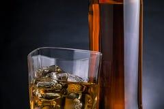 Close-up van whisky met ijsblokjes in glas dichtbij fles op zwarte achtergrond, koude atmosfeer royalty-vrije stock afbeelding