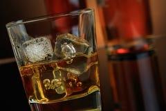 Close-up van whisky met ijsblokjes in glas dichtbij fles op zwarte achtergrond, warme atmosfeer stock afbeelding