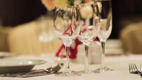 Close-up van wijnglazen scène Lege wijnglazen in elegant restaurant op achtergrond van mooi boeket van bloemen stock footage