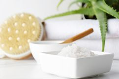 Close-up van witte container met badzout, container met klei en lepel daarin, stapel van witte handdoeken, groene installatie als royalty-vrije stock afbeeldingen