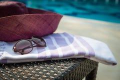Close-up van witte en purpere Turkse handdoek, zonnebril en strohoed op rotanlanterfanter met blauw zwembad als achtergrond Stock Fotografie