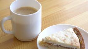 Close-up van witte mok en plaat met kaastaart Ochtendontbijt met koffie en klassieke kaastaart op houten lijst stock footage
