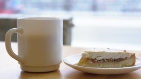 Close-up van witte mok en plaat met kaastaart Ochtendontbijt met koffie en klassieke kaastaart op houten lijst stock video
