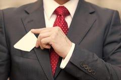 Close-up van Zakenmanhand die een adreskaartje over kostuumzak houden die op wit wordt geïsoleerd Zakenman in kostuum en rode ban royalty-vrije stock fotografie