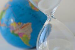 Close-up van zandloper met aarde op de achtergrond - Verontreiniging, ecologie, het globale verwarmen, klimaatveranderingconcept royalty-vrije stock foto's