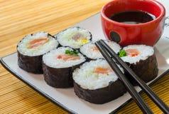 Close-up van zes sushibroodjes met sojasaus en eetstokjes Royalty-vrije Stock Afbeeldingen