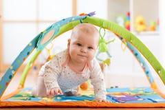 Close-up van zeven van het babymaanden meisje die op kleurrijke playmat kruipen Stock Fotografie