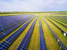 Close-up van zonnepanelen op groen gras met blauwe hemel Stock Afbeeldingen
