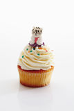 Close up of vanilla buttercream cupcake with cat figurine agains Royalty Free Stock Image
