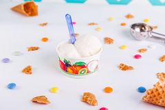 Close up Vanilla Ice-cream in a paper cup on the white background with colorful candies, pieces of waffles, ice cream spoon. And empty ice cream cone. Selective Stock Photos