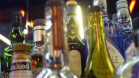 Close-up of variety of alcohol in bar. Frame. Colorful glass bottles stand on bar counter on background of bright lamps stock footage