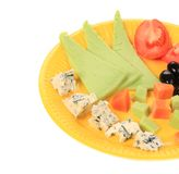 Close up of Various cheese on yellow platter Stock Photography
