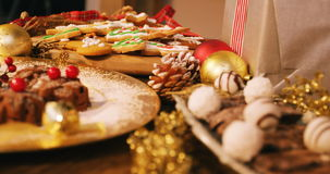Close-up of various christmas desserts and gifts. On wooden table 4k stock video footage