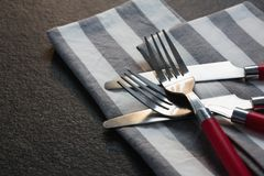 Various cutlery and folded napkin on concrete background. Close-up of various cutlery and folded napkin on concrete background Royalty Free Stock Image