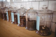 Close up of various food in glass jars with labels at coffee shop royalty free stock images
