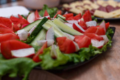 Close up of various fresh cut vegetables on black plate on table Stock Image