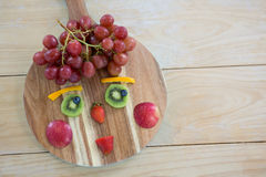 Close-up of various fruits on chopping board on wooden table Royalty Free Stock Photos